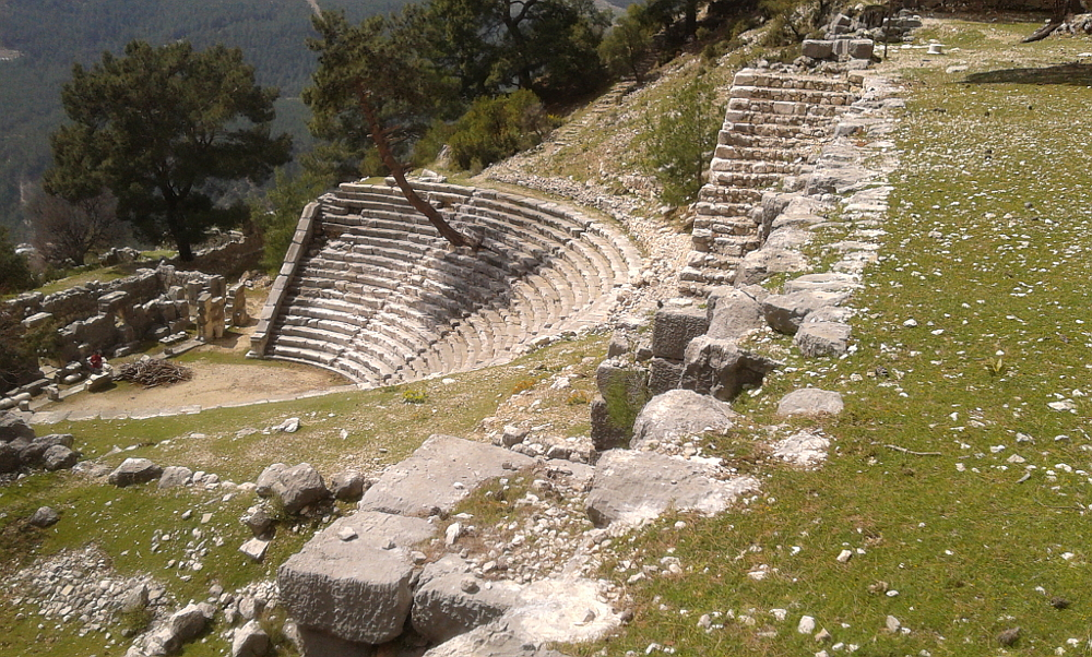 The theatre is below the open side of the half stadium. Note the tree growing out of the seating